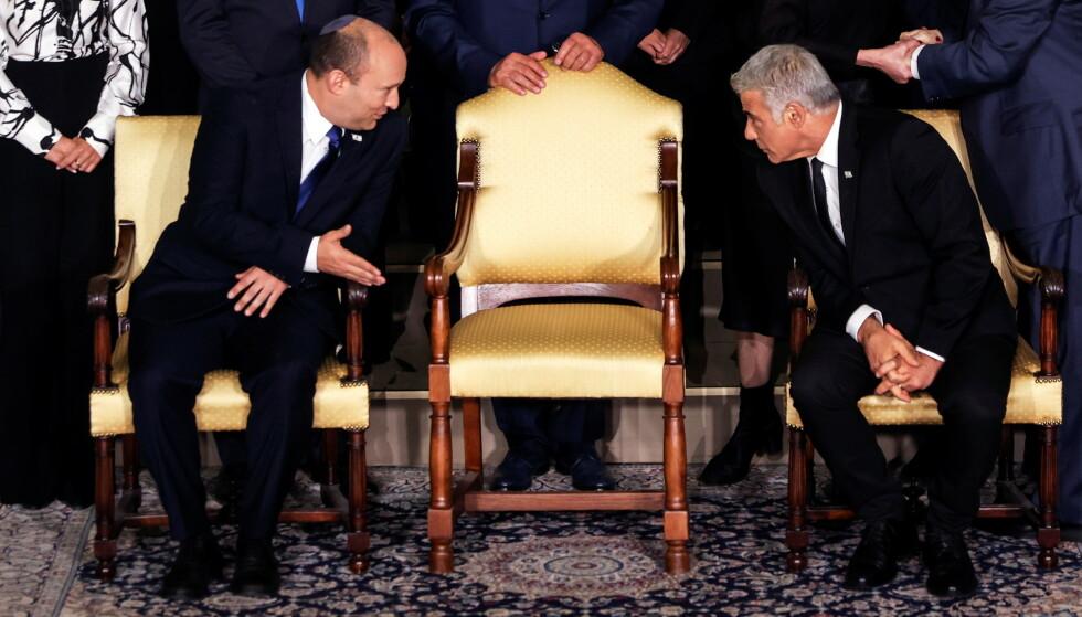 NY REGJERING: Israels statsminister Naftali Bennett tar en prat med sin utenriksminister Yair Lapid før den nye regjeringen skulle bli avbildet i Jerusalam mandag. Om to år skal de to bytte posisjon, om alt går som de ønsker. Foto: Reuters / NTB