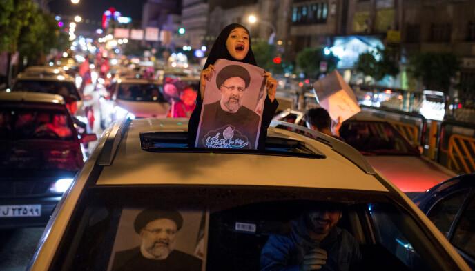 NYTT FORSØK: Her holder en jente en valgplakat av presidentkandidat Ebrahim Raisi i Teheran i 2017, da han forsøkte å bli president. Raisi fikk nesten 16 millioner stemmer, men tapte for den mer moderate kandidaten og nåværende president, Hassan Rouhani. Nå stiller Raisi til valg igjen, som klar favoritt. Foto: Reuters / NTB