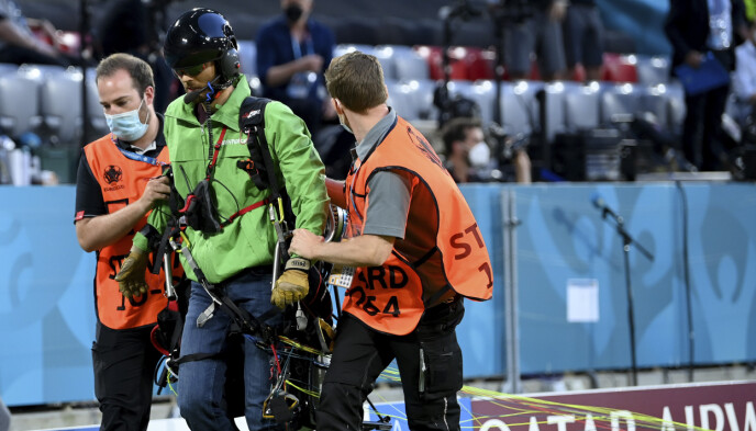 LEDES VEKK: Fallskjermhopperen ble ledet vekk fra stadion i München etter stuntet sitt. Foto: Matthias Hangst/Pool via AP.