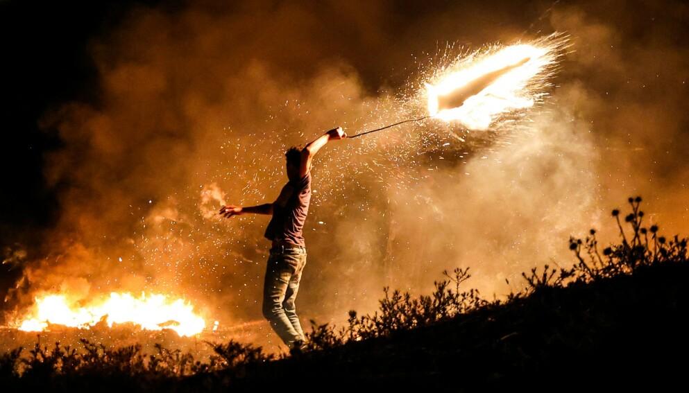 PROTESTERER IGJEN: En palestinsk demonstrant kaster en brennende prosjektil fra Gaza mot Israel. Palestinerne kastet brennende ting og brannballonger mot og inn i Israel som en protest mot at ultranasjonale tirsdag hadde flaggmarsj i Jerusalem for å markere at Israel tok kontroll i Øst-Jerusalem i forbindelse med 1967-krigen. Foto: AFP / NTB
