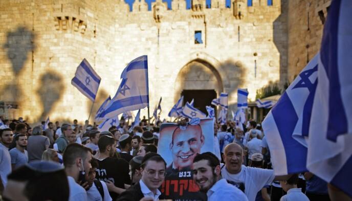 BLE ADVART: Tirsdag gjennomførte ultranasjonalistiske jøder sin flagg-marsj i Øst-Jerusalem og gamlebyen, til tross for advarsler om at nettopp det kunne føre til en ny eskalering i konflikten med palestinerne. På plakaten pryder Naftali Bennett, tidligere bosetterleder, og nå fersk statsminister i Israel. Foto: AFP / NTB