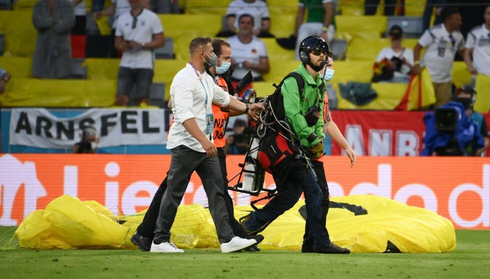 LEDES VEKK: Fallskjermhopperen ble ledet vekk fra stadion i München etter stuntet sitt. Foto: AFP.