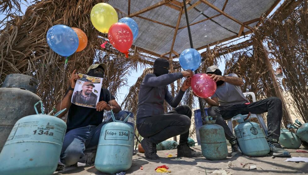 EKSPLOSIVER OG BRENNBAR VÆSKE: Eksplosiver og brennbar væske festes på snorer til heliumballongene. Foto: Mahmud Hams / AFP / NTB