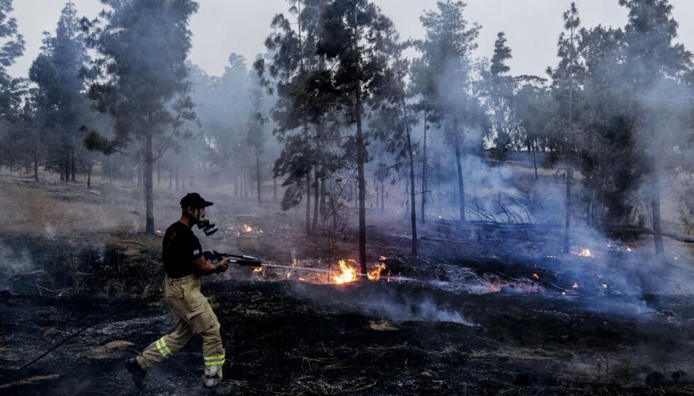 SLOKKER: En israelsk brannmann kjemper mot flammer forårsaket av brannballonger fra Gazastripen. Foto: Tsafrir Abayov / AP / NTB