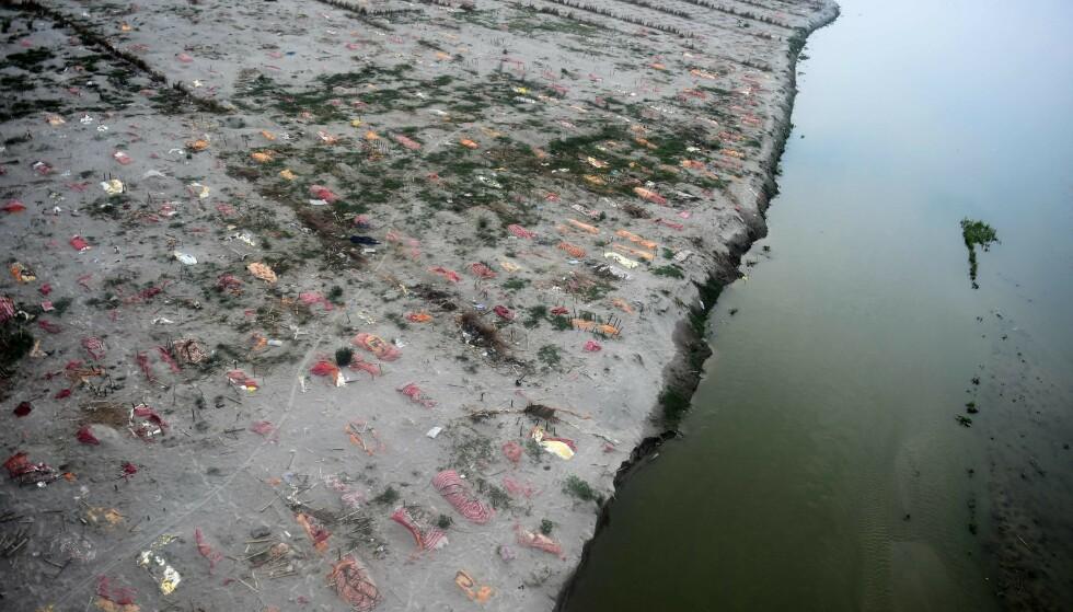 SNART UNDER VANN: Ved Phafamau ghat ligger de døde synlige, rett ved elva, kun dekket av tøyklede. Regntiden kan gjøre at alle havner under vann. Foto: SANJAY KANOJIA / AFP / NTB