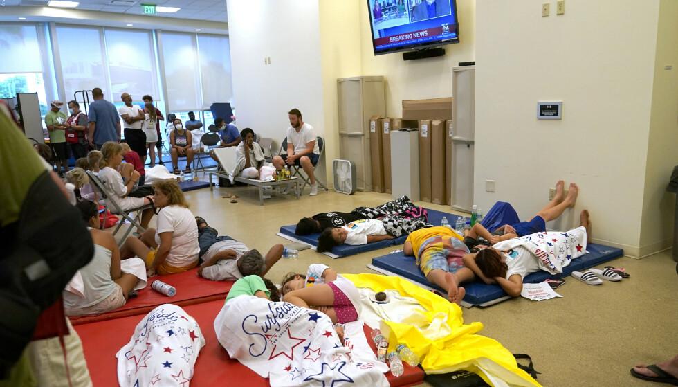 SAMLET: Folk ligger på gulvet og håper på godt nytt i et senter for gjenforening av familier i Miami. Foto: Lynne Sladky / AP / NTB