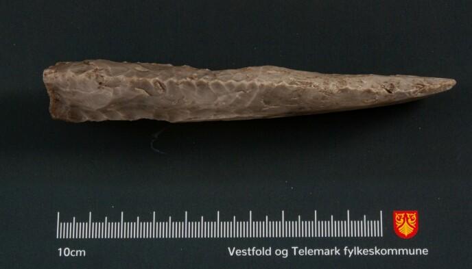FLINTDOLK: Steinen som viser seg å være en flintdolk er tolv cm lang og to cm bred. Foto: Vestfold og Telemark fylkeskommune