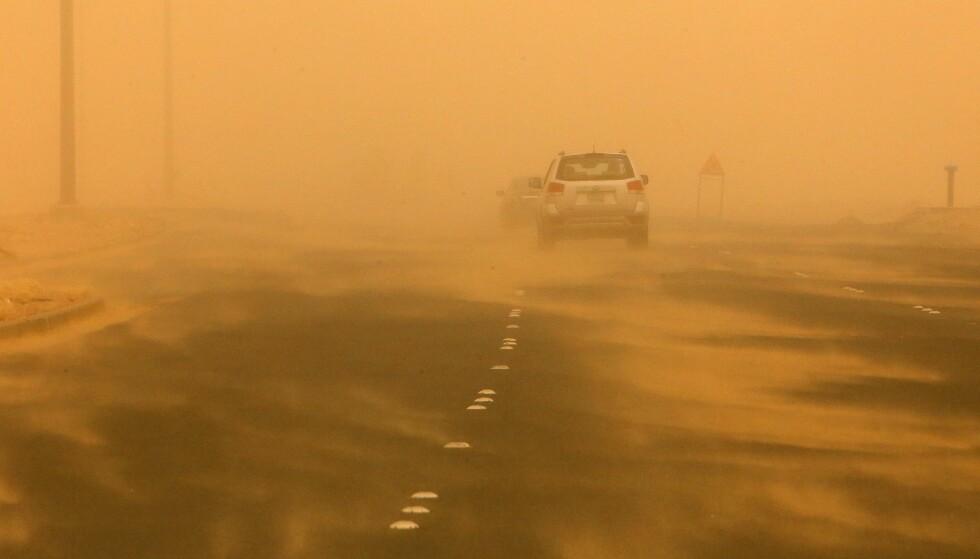 STORM: Kjøretøy kjører langs en motorvei, nord for Kuwait, under sandstorm 17. juni 2021. Foto: YASSER AL-ZAYYAT/AFP/NTB.