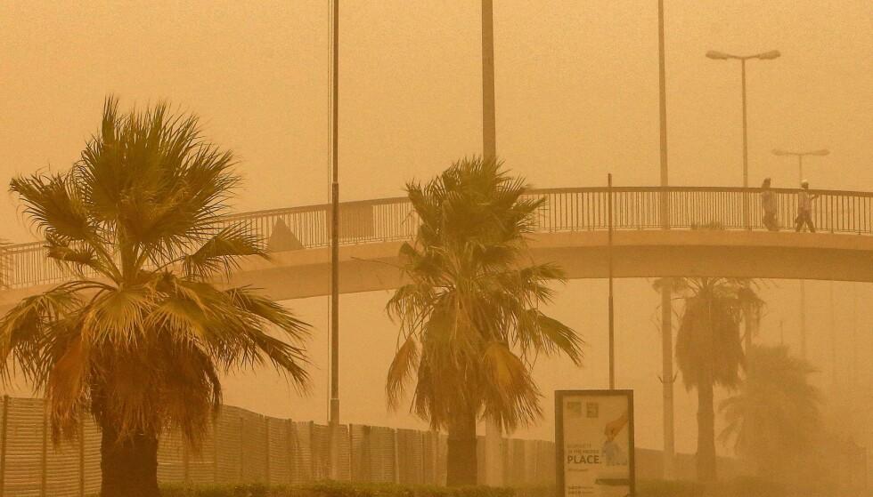 DÅRLIG SIKT: Folk krysser gangbro under sandstorm 17.juni. Foto: YASSER AL-ZAYYAT /AFP/NTB.