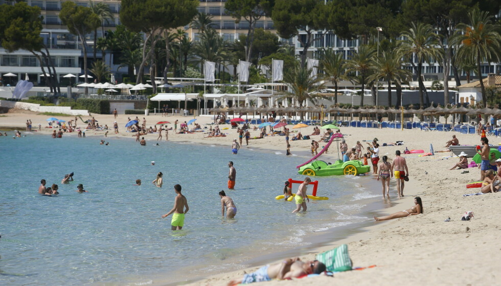 SMITTEN STIGER: Folk koser seg på Magaluf-stranden på Mallorca. Imidlertid stiger smitten. Foto: Enrique Calvo/ Reuters.
