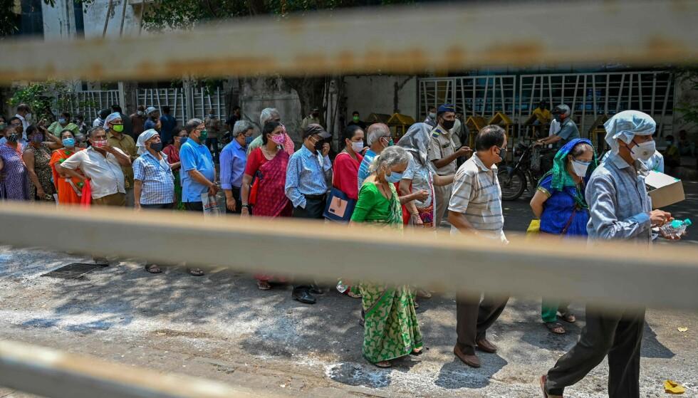 VAKSINEKØ: Flere personer i kø for å få coronavaksinen i Mumbai tidlig i mai, rundt da svindelen skal ha startet. Foto: Punit Paranjpe / AFP / NTB