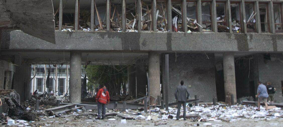 Oslo 20110722. TERROR RAMMER NORGE. Eksplosjon i Regjeringskvartalet der en bombe gikk av fredag ettermiddag. Høyblokken og store deler av området rundt ble rammet av den kraftige bombeeksplosjonen. Flere mennesker ble såret eller drept. Bildet:  Inngangspartiet til statsministerens kontor like etter bomben smalt fredag, med rester av bombebilen til venstre i bildet.  FOTO: Morten Holm / SCANPIX
