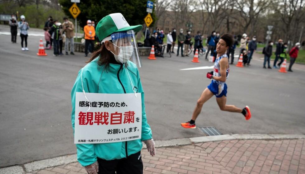 BESKJED: En frivillig bærer et skilt som ber folk holde seg unna konkurransen for å stoppe spredningen av coronaviruset. Foto: AFP.