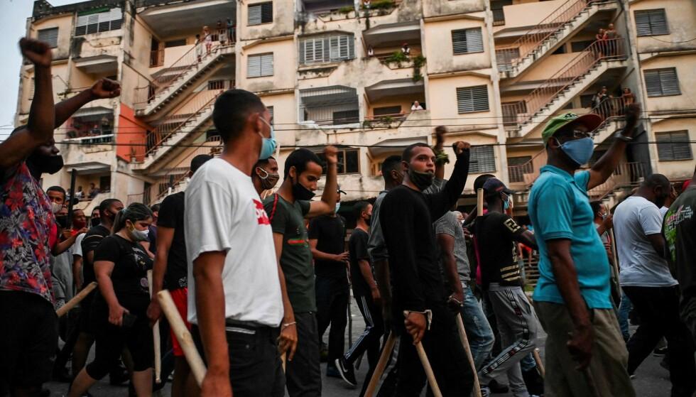 KØLLER: Såkalte «revolusjonære» kubanere væpnet med køller av tre inntok gatene for å vise støtte til president Miguel Díaz-Canel og hans regjering i bydelen Arroyo Naranjo i utkanten av Havana 12. juli. Dagen før hadde Cuba opplevd de største demonstrasjonene mot regimet på 30 år. Foto: YAMIL LAGE / AFP / NTB