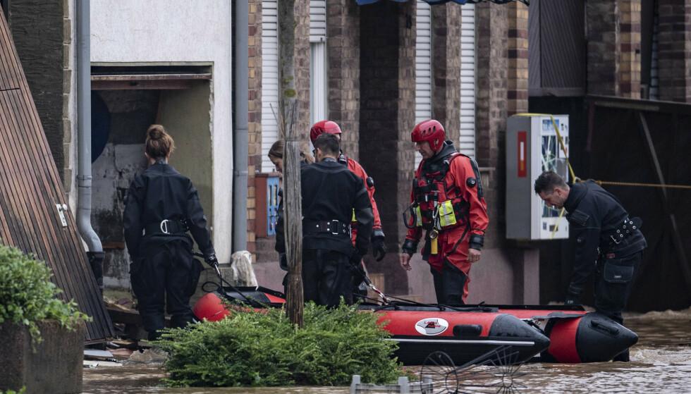 REDNINGSAKSJON: Redningsmannskaper med en oppblåsbar båt leter etter overlevende i Erfstadt i Tyskland. Foto: Marius Becker/dpa via AP