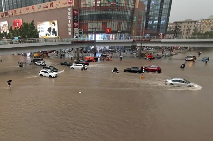 Regenachtig weer: Auto's kwamen dinsdag tot stilstand tijdens overstromingen veroorzaakt door stortregens in Zhengzhou, een stad met een miljoen inwoners in centraal China.  Foto: Chinatopix via AP/NTB