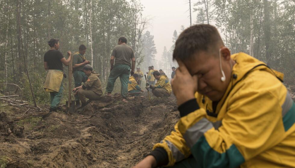 FATIGUÉ : Il y a une vaste zone que les pompiers et les bénévoles doivent garder le contrôle et essayer d'éteindre le feu de forêt qui fait des ravages.  Photo : Alexey Vasilyev / NTB