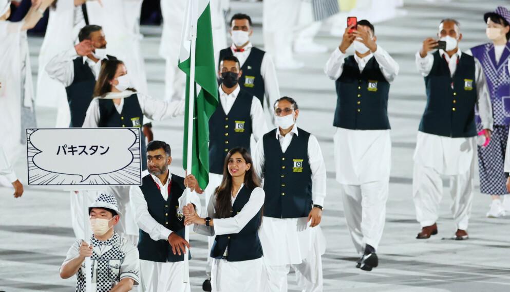 GA BLAFFEN: Flaggbærerne til Pakistan - Khalil Akhtar og Mahoor Shahzad - hadde ikke på seg munnbind under åpningsseremonien. Foto: NTB