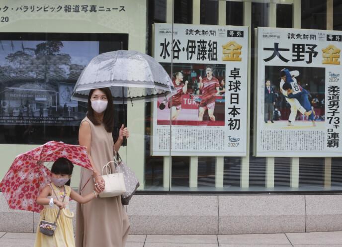 PÅBUDT MED MUNNBIND: Tokyo forsøker å få til et dagligliv samtidig som OL arrangeres. Personer fra over 200 nasjoner er samlet i byen, noe som øker faren for virusspredning. Foto: NTB