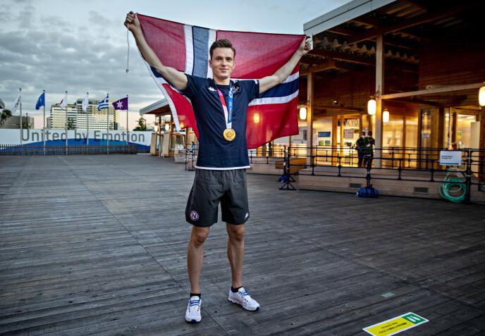 RØDT, HVITT OG FLOTT: Karsten Warholm holder oppe flagget i OL-landsbyen. Verdens raskeste 400 meter hekk-løper kommer fra Norge.