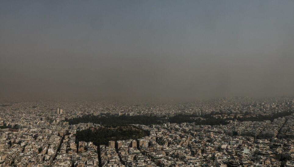 INNHYLLET I RØYK: Tjukk røyk fra brannene som raser i den ekstreme varmen i Hellas, har lagt seg som et lokk over hovedstaden Aten onsdag. Foto: Giannis Panagopoulos / Eurokinissi / Reuters / NTB