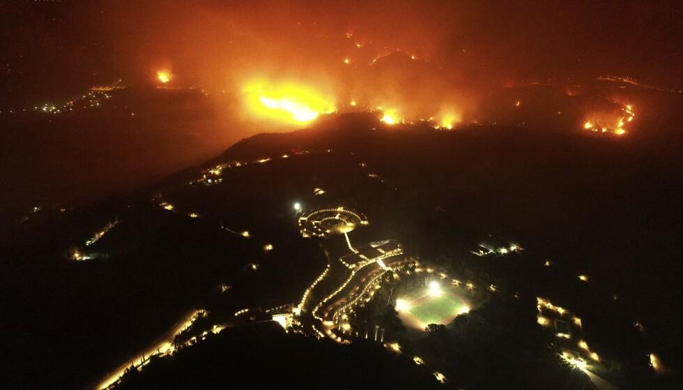 I BRANN: Her kan man se skogbrannen nærme seg Olympia stadion i Hellas. Foto: Giannis Spyrounis / AP / NTB