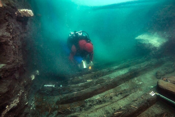 RESTER: En dykker undersøker restene av et gammelt militærfartøy som ble oppdaget i den nedsunkne byen. Foto: AFP / NTB