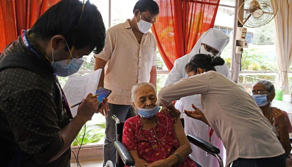 DEN TREDJE VERDEN: En fattig eldre kvinne i Mumbai får en dose av den indiskproduserte Covaxin-vaksinen. Foto: Ashish Vaishnav / SOPA Images / Shutterstock / NTB
