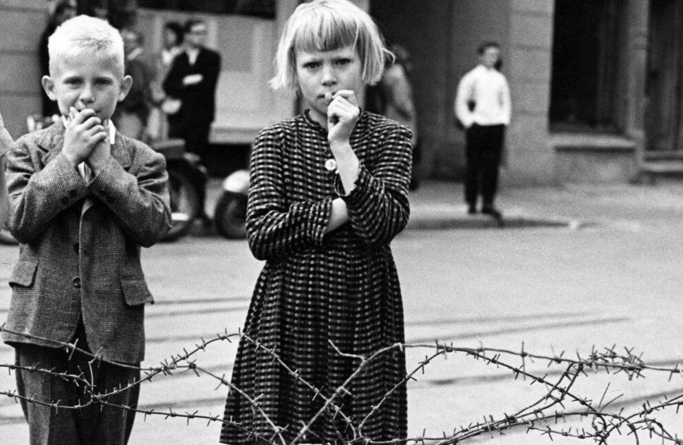SKAMMENS MUR: I august 1961 var byggingen av Berlin-muren, som skal skille Øst- og Vest-Berlin, i gang. Enkelte steder er det foreløpig bare en godt bevoktet piggtråd som deler Berlin. Foto: UPI / NTB / arkiv