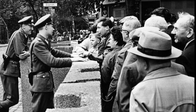 STRAMMET INN: 23 august stengte kommunistene enda flere grenseoverganger mellom Øst-og Vest-Berlin. Antallet overganger ble redusert fra 13 til 8, og bare diplomater, utlendinger og medlemmer av de vestlige allierte styrker kunne fra da av bevege seg fritt over grensen uten spesiell tillatelse. Her snakker vest-berlinere med øst-tysk politi over den provisoriske muren. Foto: UPI / NTB / arkiv