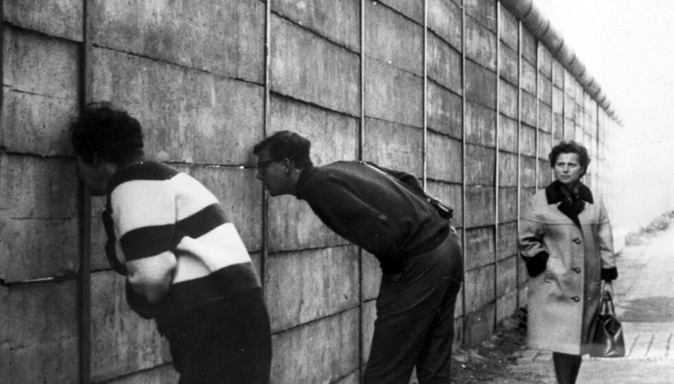 KIKKER: I Lindenstrasse i nærheten av Check Point Charlie, er den nye Berlin-muren nesten ferdig. Muren er nå tre meter høy og er avrundet på toppen, så det er vanskelig å få tak hvis noen skulle ønske å klatre over. Vestberlinere kikker inn i Øst-Berlin gjennom sprekker i muren. Foto: Keystone / Billedsentralen