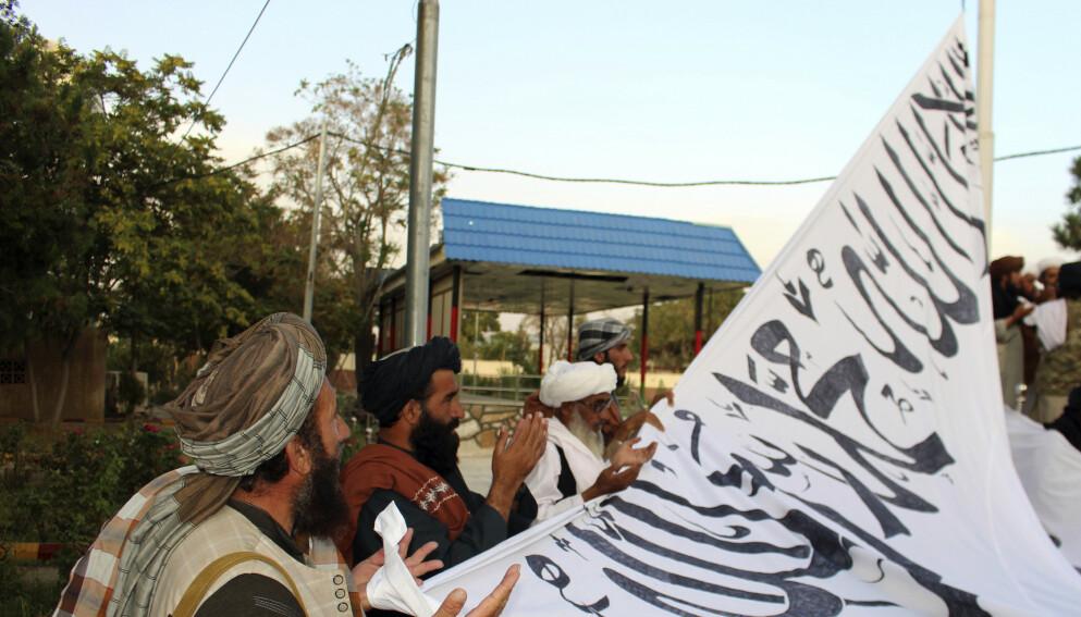 FLAGGET TIL TOPPS: Talibansoldater i bønn reiser bevegelsens hvite flagg utenfor guvernørboligen i Ghazni. Foto: Gulabuddin Amiri/AP/ Scanpix NTB
