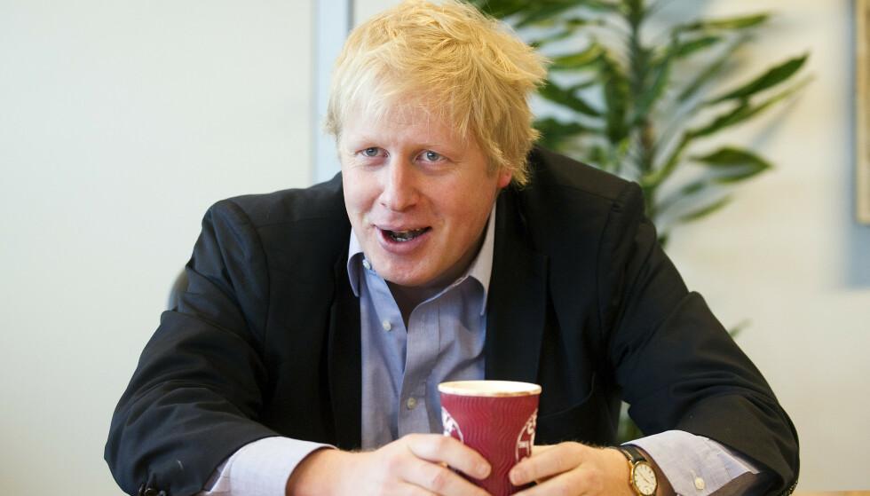 ET VANLIG SYN: Den plommerøde Costa Coffee-koppen popper opp overalt. Her er Boris Johnson i City Hall i 2010, da han var borgermester i London. Arkivfoto: Geoff Pugh/REX/NTB