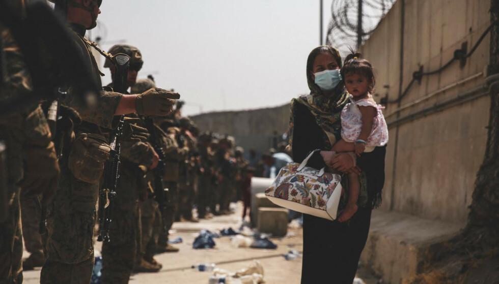 VIL BORT: Amerikanske soldater passer på at internasjonale og afghanere med riktig pass og billett ut av landet får dra fra Kabul. Som denne kvinnen og barnet. De tør ikke ta sjansen på et Afghanistan med Taliban, slik gruppa var da de styrte forrige gang, på 1990-tallet. Foto: AFP / NTB
