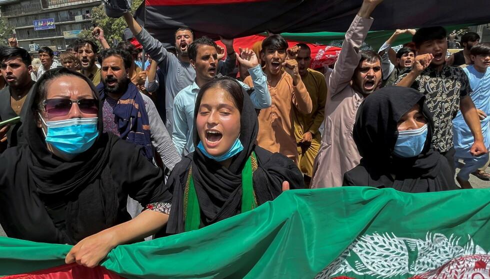 STOLTE AV FLAGGET: Afghanere holdt opp det afghanske flagget da de markerte uavhengighetsdagen i hovedstaden Kabul torsdag. Vil de kunne gjøre det i fortsettelsen, når Taliban fester grepet? Framtida lurer alle på nå. Foto: Reuters / NTB
