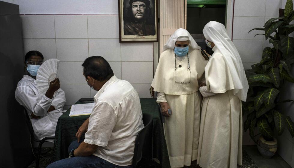 VAKSINERT: To nonner etter å ha blitt vaksinert på et vaksinesenter på Cuba med bilde av Che Guevara på veggen bak. Foto: Ramon Espinosa / AP / NTB