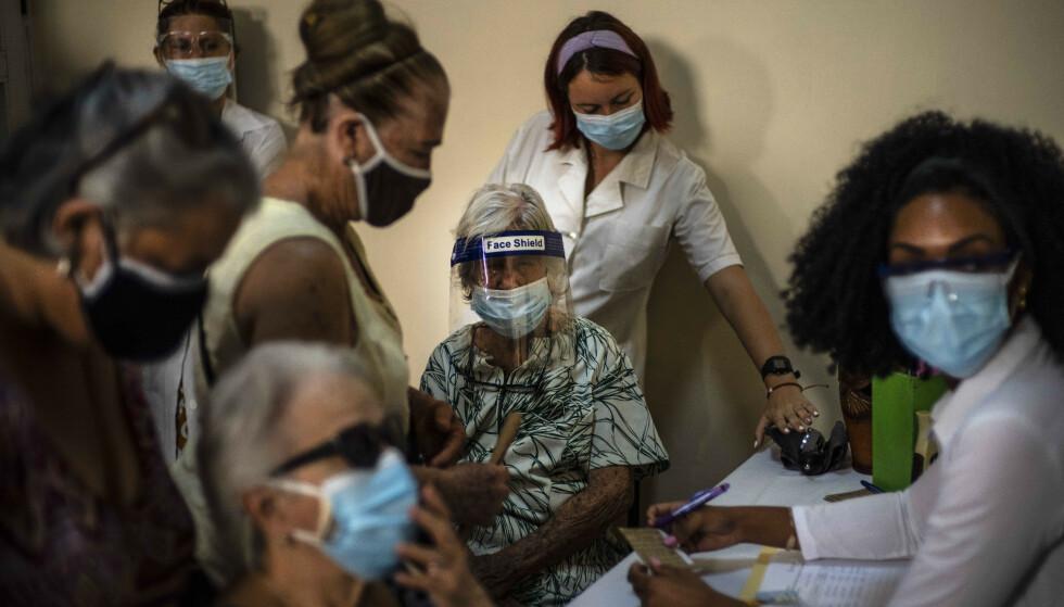 ØNSKER VAKSINE: Cuba har nå den tredje høyeste vaksinasjonsgraden i Latin-Amerika, med 25 prosent av befolkningen fullvaksinert. Her fra et vaksinersenter i Havana, der befolkningen melder seg opp til vaksinetimer. Foto: NTB / AP Photo / Ramon Espinosa