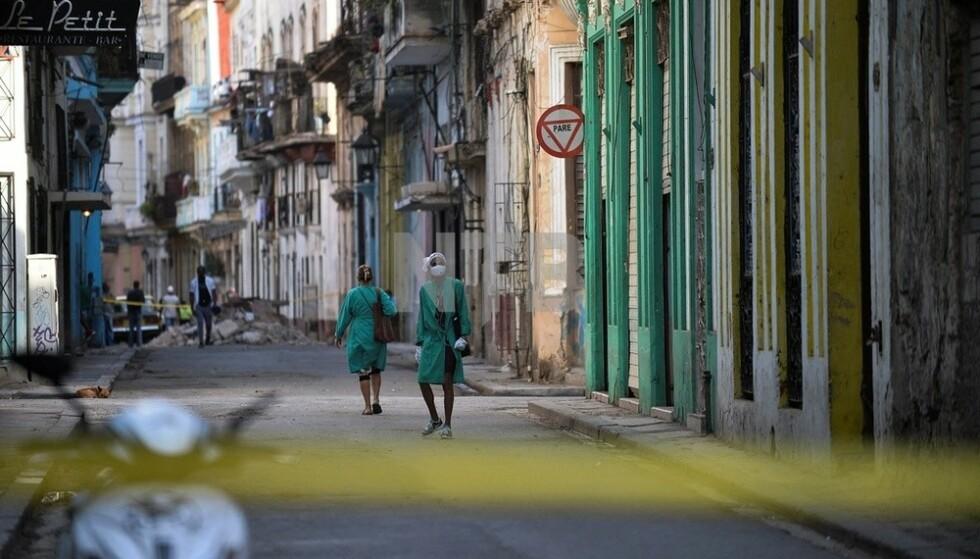 SMITTETILFELLER: Cuba har de siste månedene gått gjennom den hardeste fasen så langt i coronapandemien. Avbildet er helsepersonell som går langs en stengt gate etter at flere smittetilfeller ble registrert i april. Foto: NTB / YAMIL LAGE / AFP