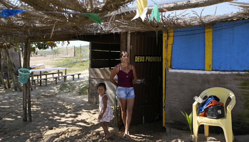 ELVEN: Vanessa Gomes Barreto og datteren står ved hyttedøra ved bredden av elva Paraiba do Sul. Foto: Silvia Izquierdo/AP/NTB