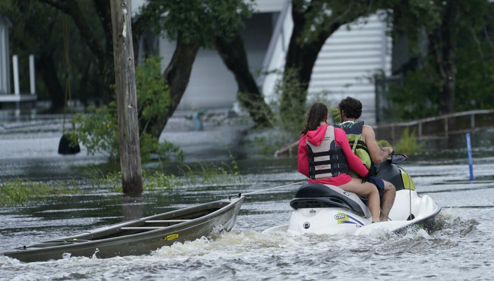 SKAPER KAOS: Innbyggere på vannscooter frakter en kano til et hus under flom i Mississippi, der Ida også skaper kaos. Foto: Steve Helber / AP / NTB