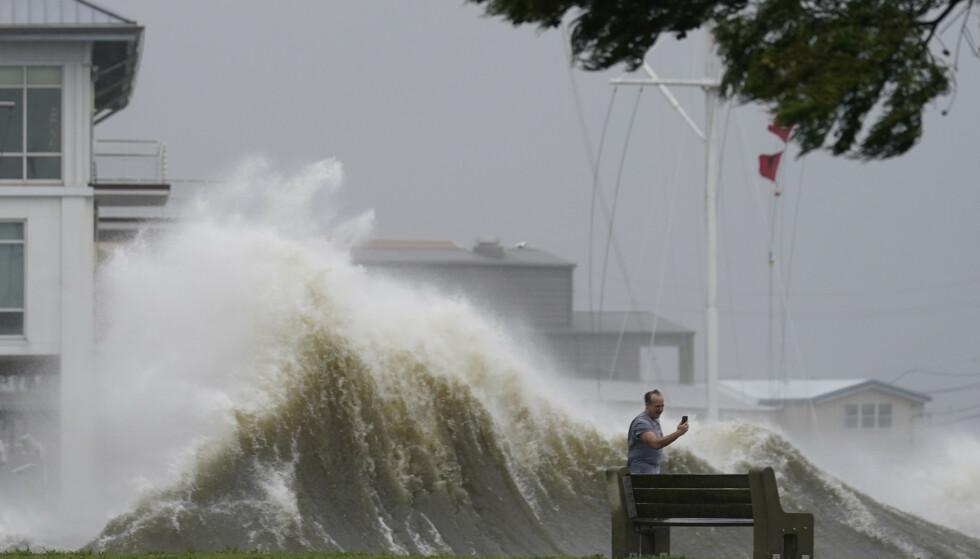 NATURKREFTER: En mann tar bilde av de store bølgene i New Orleans idet orkanen Ida skyller innover land i Louisiana. Foto: NTB / AP Photo / Gerald Herbert