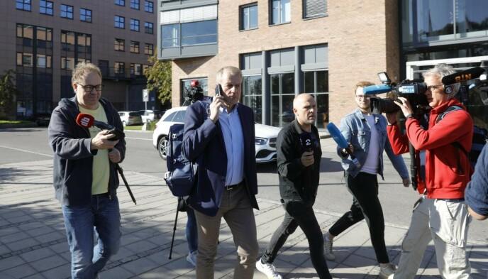 I TELEFONEN: Skipresident Erik Røste hastet ut fra møtet med et pressekorps rundt seg. Foto: Nina Hansen