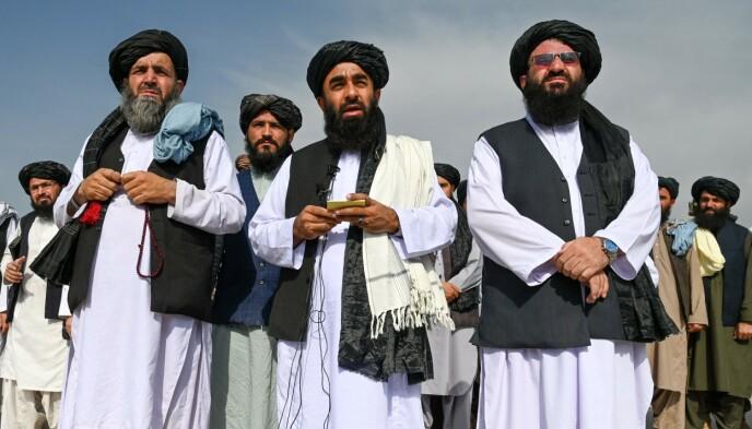 Taliban-talsmann Zabihullah Mujahid (midten) dukket opp på Kabul-flyplassen timer etter at amerikanerne var ute av landet. - Gratulerer til Afghanistan... seieren tilhører oss alle, sier han. Foto: AFP / NTB