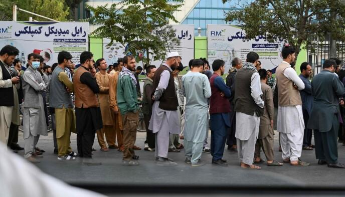 TOMME FOR KONTANTER: Afghanere står i kø i håp om at bankene i Afghanistan nå åpner, etter at amerikanerne er ute av landet. Foto: AFP /NTB