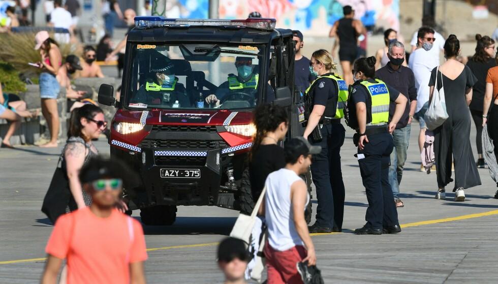 ULYDOGHET: Politiet avbildet mens de prøver å begrense at folkemengder samler seg påSt Kilda Beach i Melbourne. Foto: William WEST / AFP /NTB
