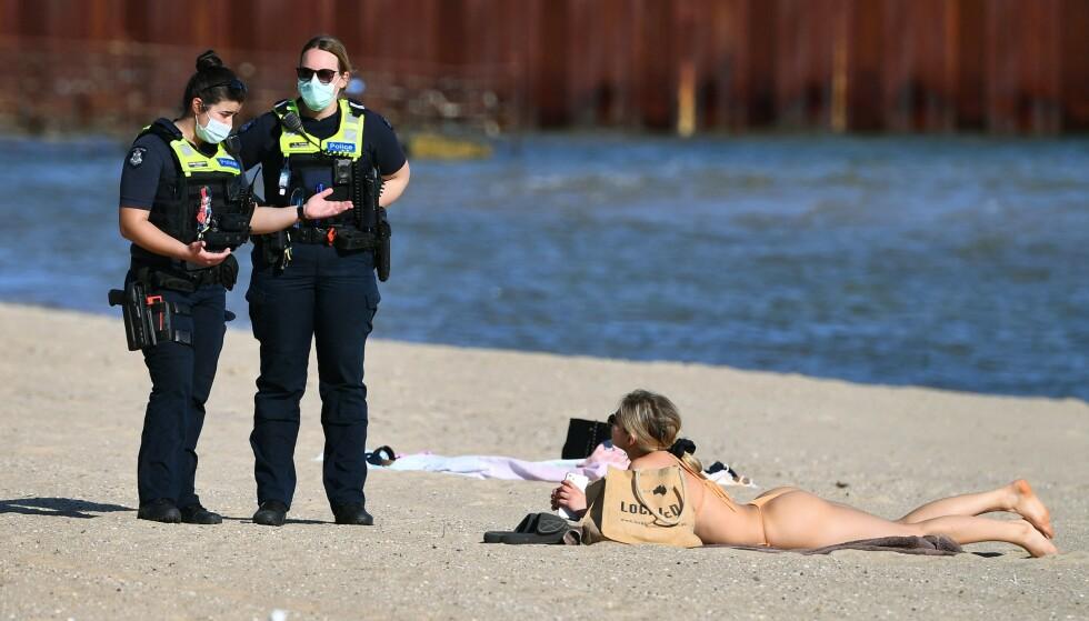 TILSNAKK: Politiet gir tilsnakk til en kvinne på St Kilda Beach. Foto: William West /AFP / NTB