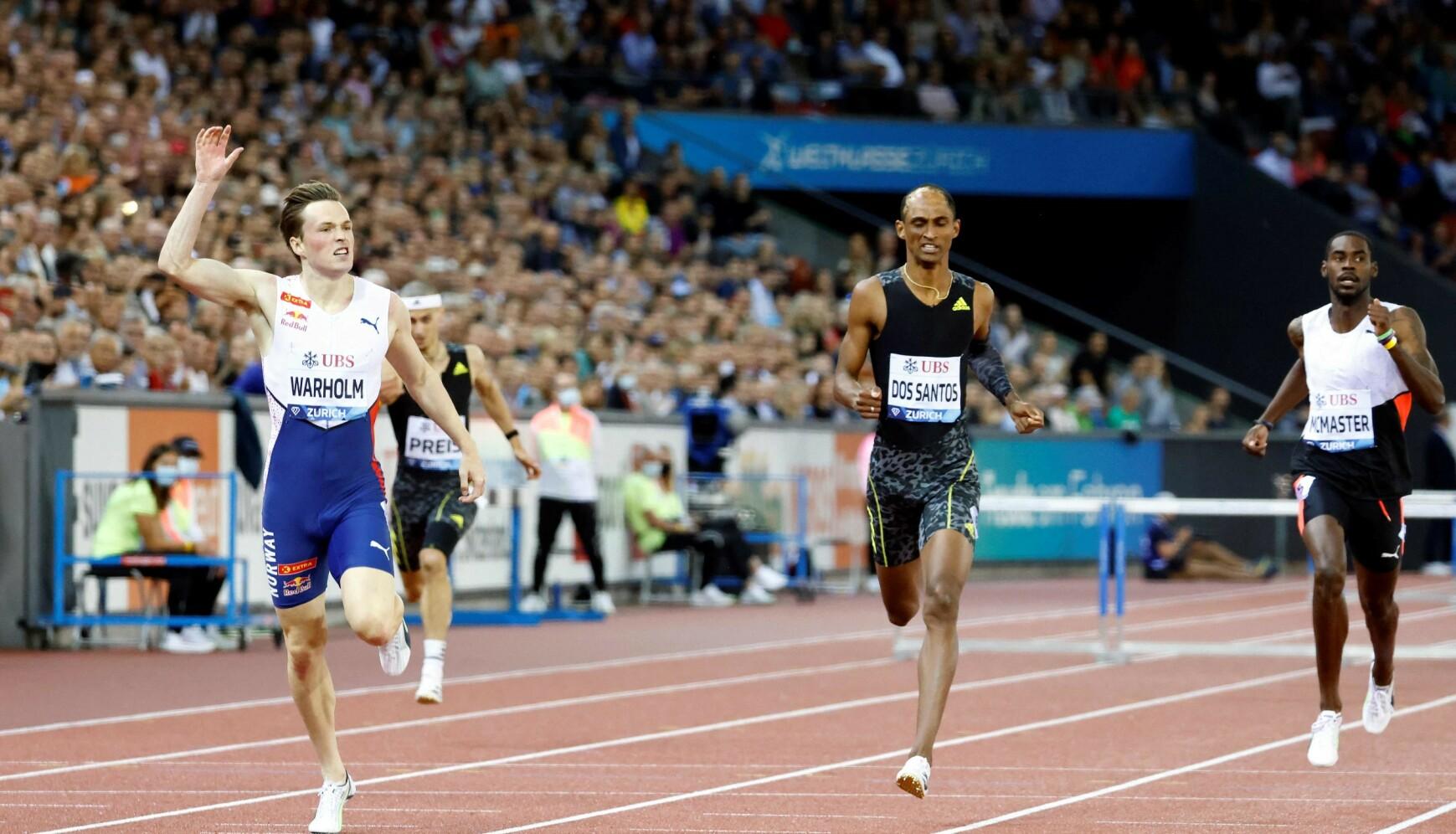 ØYEBLIKKET: Karsten Warholm løper over mållinja foran Dos Santos. Foto: Stefan Wermuth / AFP)