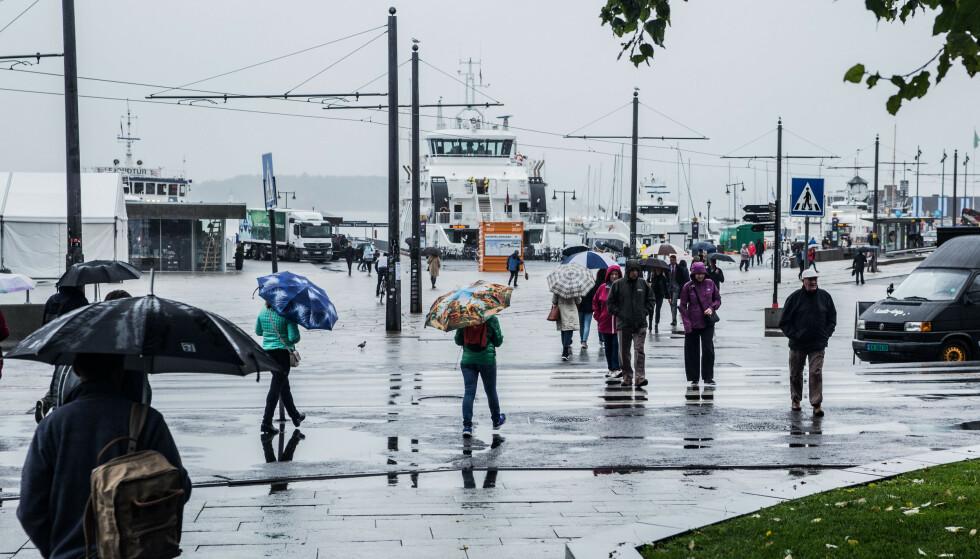 HØST: Nå må man finne fram høstjakkene. Temperaturene faller, og vi kan forvente nedbør øst og sør i landet, som her på en regntung dag på Aker Brygge i Oslo. Foto: Mariam Butt / NTB