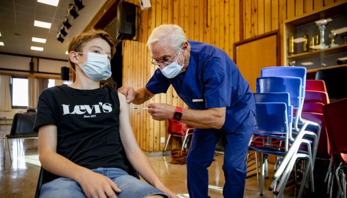 SÅNN: Lege Ove Kjell Andersen ved bydel Nordstrands vaksinesenter setter raskt dosen i Martin Aspehjell Eikelands (12) overarm. Aulaen på Brannfjell skole i Oslo er gjort om til vaksinesenter for dagen.