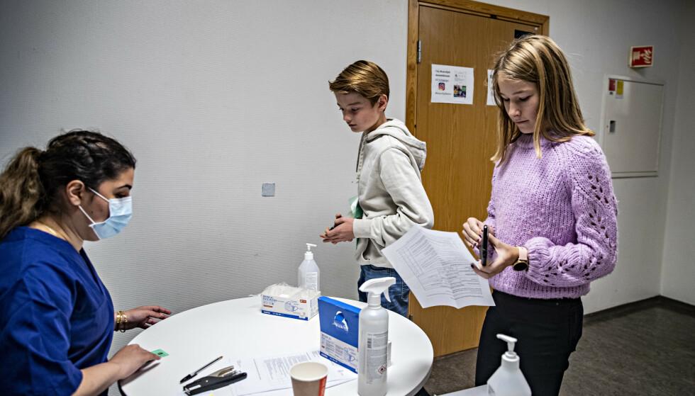 REGISTRERES: Elevene Martin Aspehjell Eikeland (12) og Elin Nordheim Nustad (13) ved Brannfjell skole i Oslo registrer seg for vaksine, på vei inn inn i aulaen på skolen.